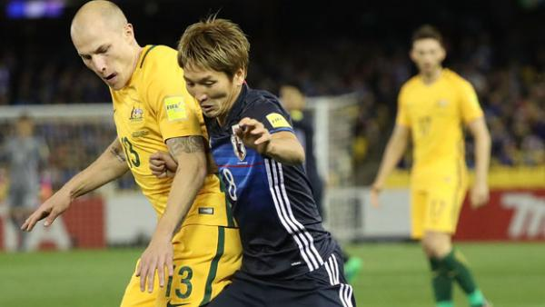 Socceroos midfielder Aaron Mooy fights for the ball with Japan's Genki Haraguchi.