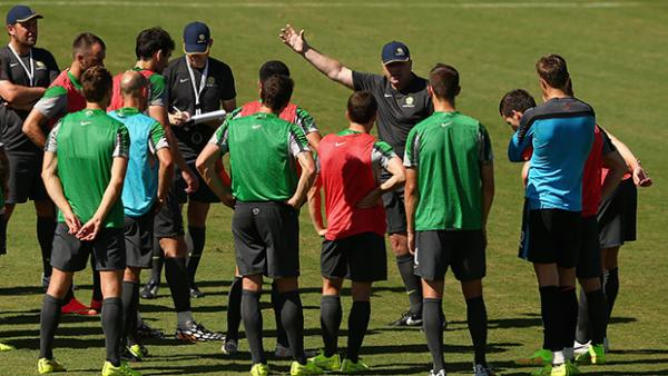 Coach Ange Postecoglou gives instructions to his Socceroos side on the training ground.
