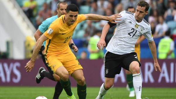Tom Rogic fights for the ball with German captain Julian Draxler.