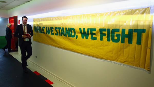 Joeys head coach Tony Vidmar walks down the tunnel with an Australian banner on display