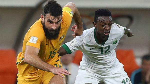 Caltex Socceroos captain Mile Jedinak challenges Saudi Arabia's Hassan Fallatah for the ball.