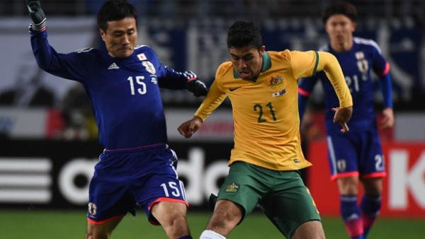 Socceroos midfielder Massimo Luongo fights for the ball with Japan's Yasuyuki Konno.
