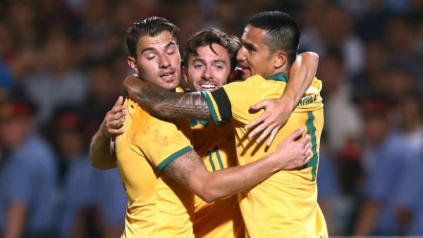 Tommy Oar is embraced by James Troisi and Tim Cahill after scoring the Socceroos second goal.