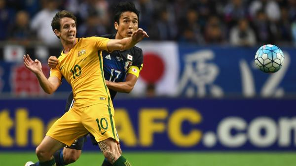 Robbie Kruse gets man-handled by his Japanese defender during the Caltex Socceroos 2-0 loss in Saitama.