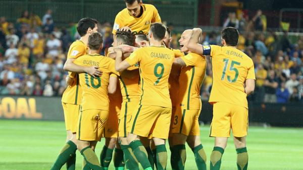 Socceroos players celebrate Massimo Luongo's early strike against Tajikistan.