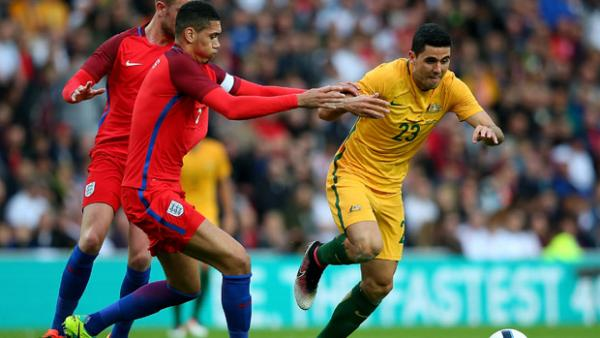 Socceroos playmaker Tom Rogic fights for the ball with England captain Chris Smalling.