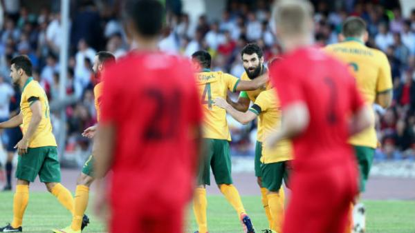 Mile Jedinak is embraced by teammates after scoring the Socceroos opener.